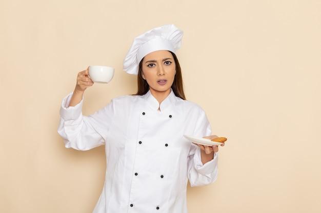 Вид спереди молодой женщины-повара в белом костюме повара, держащей чашку кофе на светло-белой стене