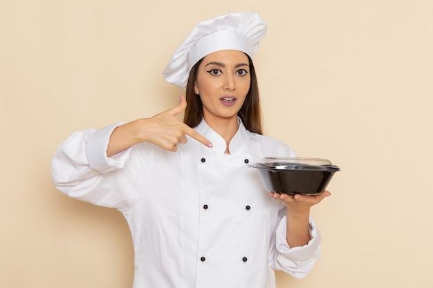 흰 벽에 어두운 그릇을 들고 흰 쿡 정장에 젊은 여성 요리사의 전면보기