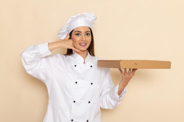 明るい白い壁にフードボックスを保持している白いクックスーツの若い女性料理人の正面図