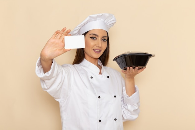 白い壁に鍋とカードを保持している白いクックスーツの若い女性料理人の正面図