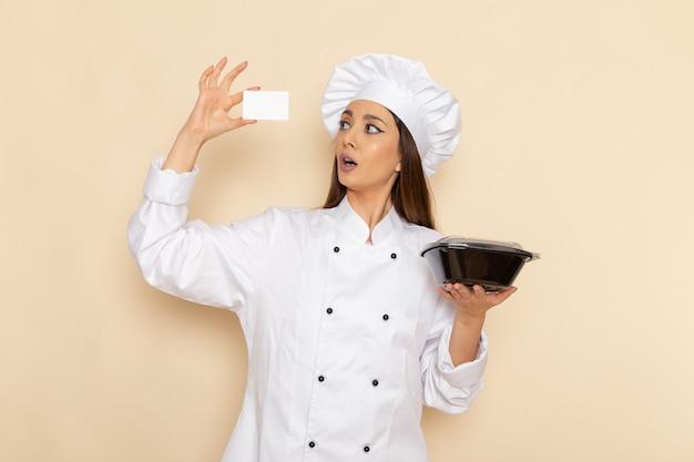 Вид спереди молодой женщины-повара в белом костюме повара, держащей кастрюлю на белой стене