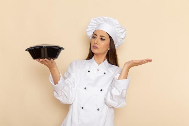 白い壁に鍋を保持している白いクックスーツの若い女性料理人の正面図