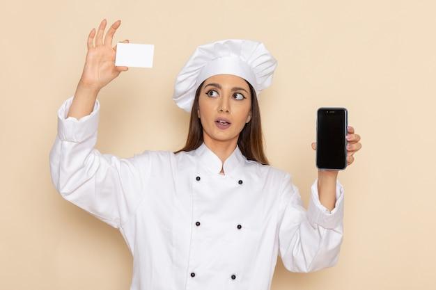 明るい白い壁に電話とカードを保持している白いクックスーツの若い女性料理人の正面図