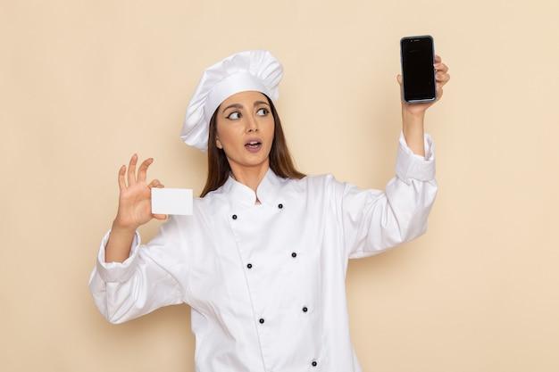 Вид спереди молодой женщины-повара в белом костюме повара, держащей смартфон и карточку на светло-белой стене