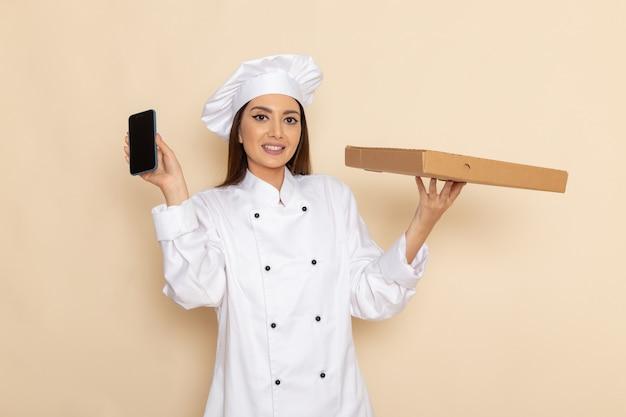 Вид спереди молодой женщины-повара в белом костюме повара, держащей смартфон и коробку для еды на белой стене