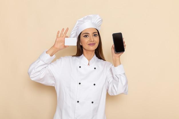 白い壁に白いカードと電話を保持している白いクックスーツの若い女性料理人の正面図
