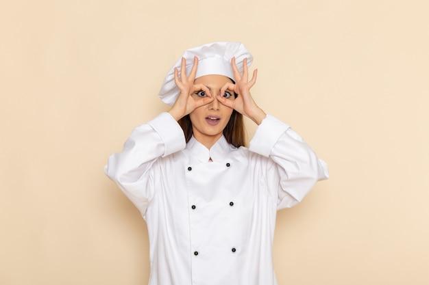 明るい白い壁に白いクックスーツの若い女性料理人の正面図