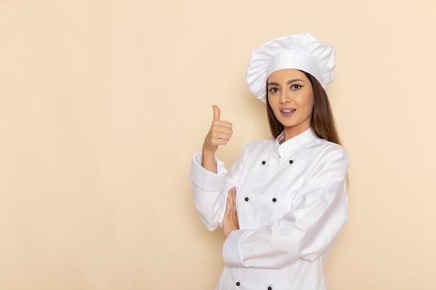 明るい白い壁にポーズと笑顔の白いクックスーツの若い女性料理人の正面図