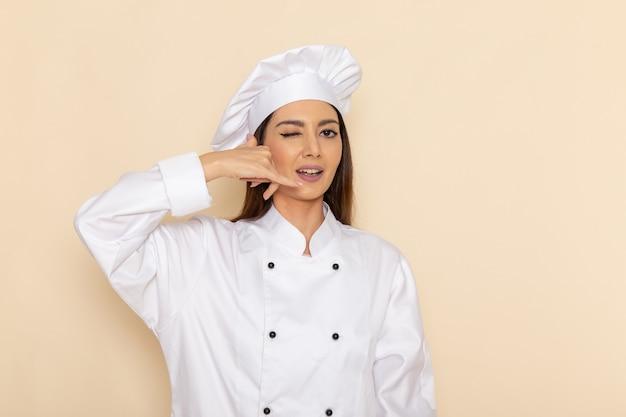 明るい白い壁にまばたき白いクックスーツの若い女性料理人の正面図