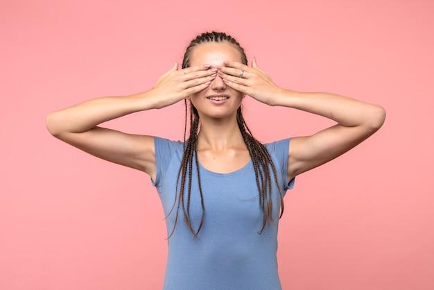 Вид спереди молодой женщины, закрывающей глаза на розовом
