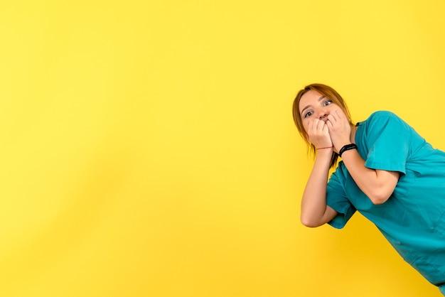 노란색 벽에 흥분된 젊은 여성 의사의 전면보기