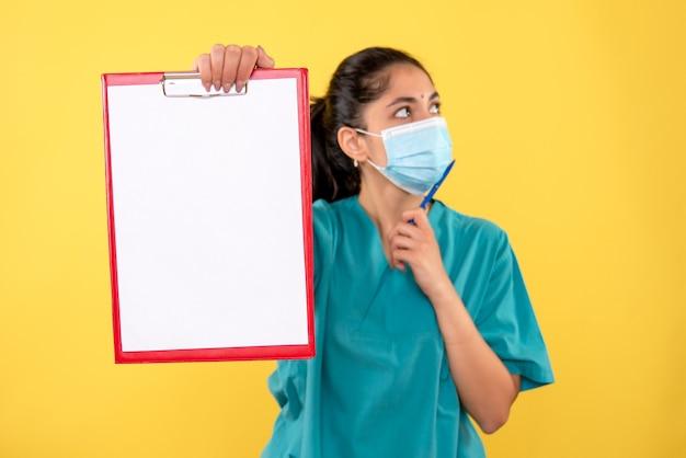 Вид спереди молодой женщины-врача, держащей буфер обмена на желтой стене