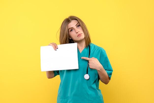 黄色の壁にファイルを保持している若い女性医師の正面図