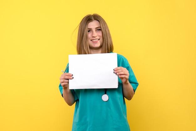 노란색 벽에 파일을 들고 젊은 여성 의사의 전면보기