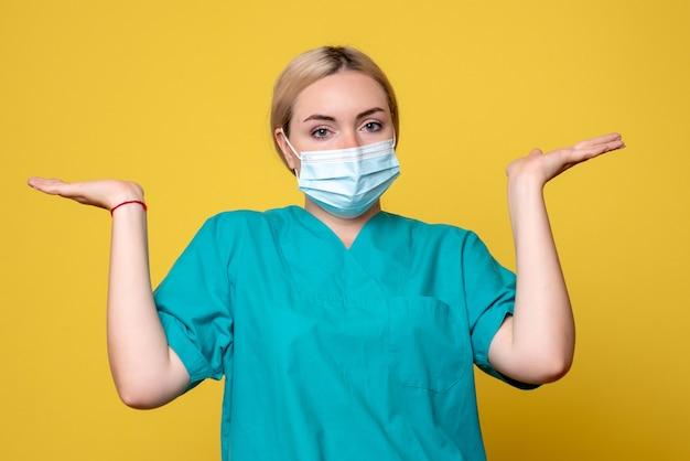 노란색 벽에 의료 셔츠와 멸균 마스크에 젊은 여성 의사의 전면보기