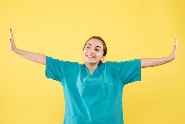黄色の壁に医療シャツを着た若い女性医師の正面図