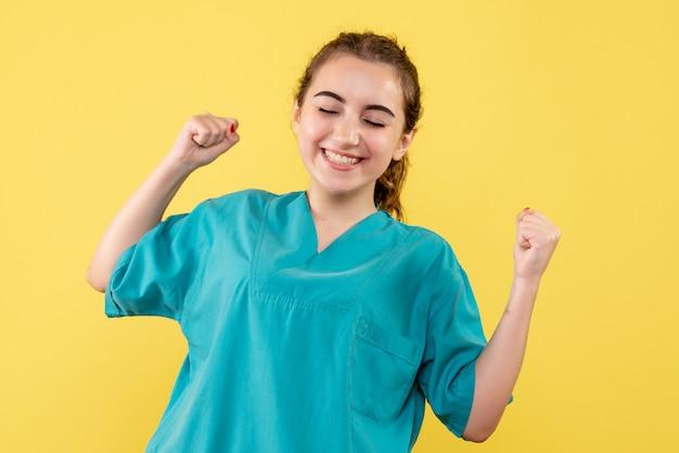 Вид спереди молодой женщины-врача в медицинской рубашке на желтой стене