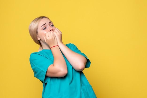 노란색 벽에 무서워 얼굴로 의료 셔츠에 젊은 여성 의사의 전면보기