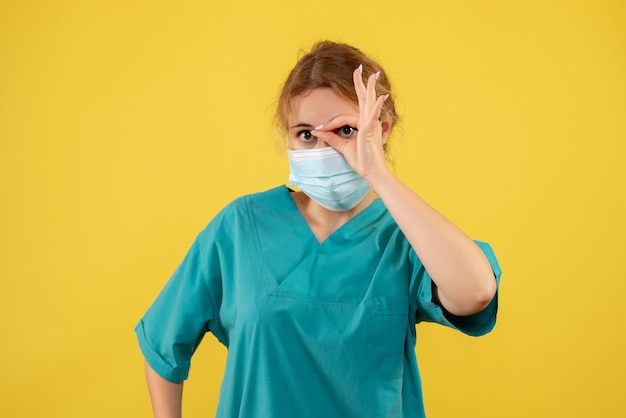 Вид спереди молодой женщины-врача в медицинском костюме и маске на желтой стене