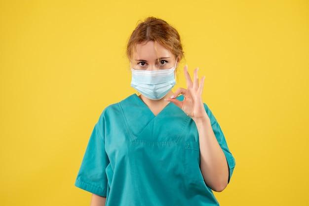 노란색 벽에 의료 소송 및 마스크에 젊은 여성 의사의 전면보기