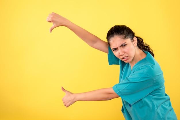 黄色の壁に親指の上下の標識を作る若い女性医師の正面図