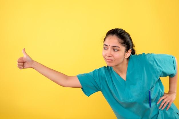 Вид спереди молодой женщины-врача, делая большой палец вверх знак на желтой стене