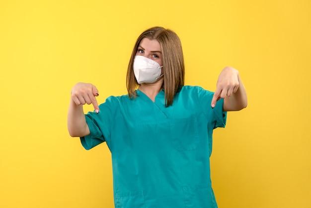 黄色の壁に若い女性医師の正面図