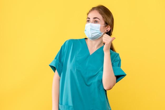 黄色の背景の健康ウイルスのパンデミックに関する若い女性医師の正面図