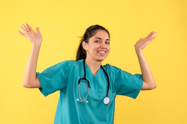 黄色の壁に手を開く若い女性医師の正面図