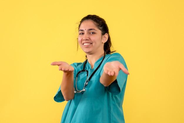 黄色の壁に何かを指している若い女性医師の正面図