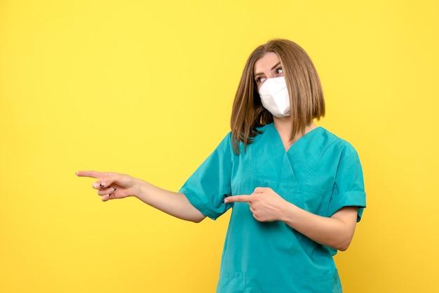 黄色の壁にマスクを持つ若い女性医師の正面図