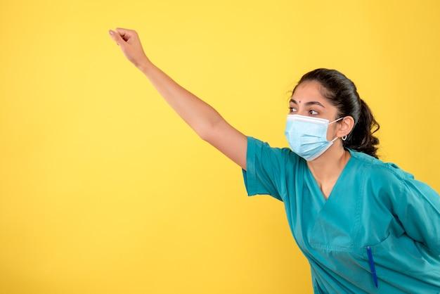 노란색 벽에 슈퍼 영웅 제스처를 만드는 의료 마스크와 젊은 여성 의사의 전면보기