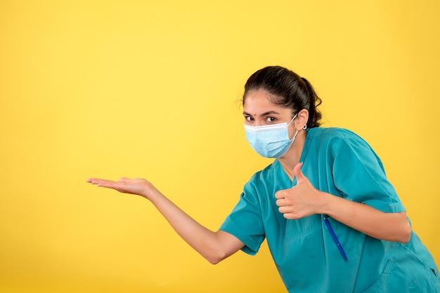 黄色の壁に親指を立てる医療マスクを持つ若い女性医師の正面図