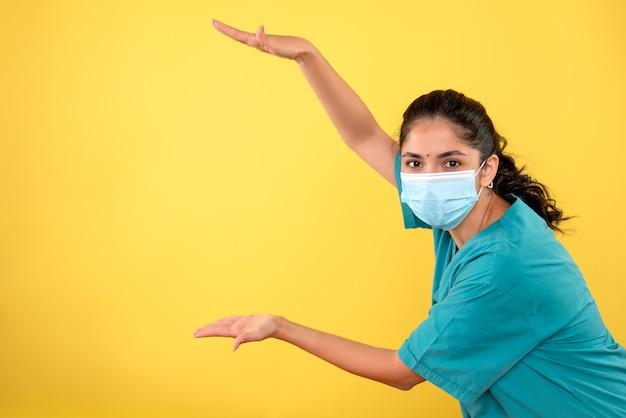黄色の壁に手でサイズを示す医療マスクを持つ若い女性医師の正面図