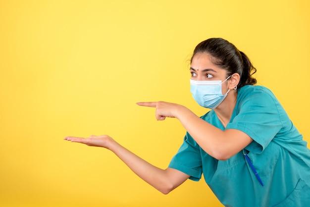 黄色の壁に立っている医療マスクを持つ若い女性医師の正面図