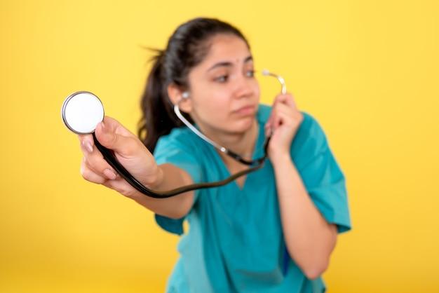 黄色の孤立した壁に聴診器を持つ若い女性医師の正面図