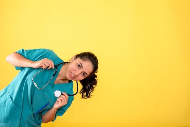 노란색 벽에 청진기를 가진 젊은 여성 의사의 전면보기