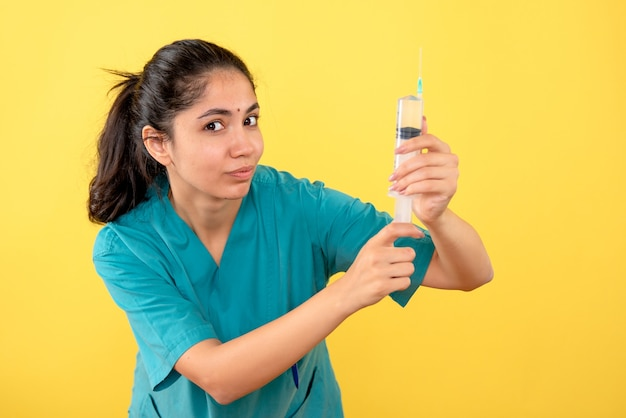 노란색 벽에 서있는 주사기와 젊은 여성 의사의 전면보기