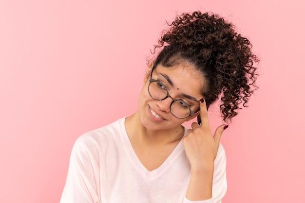 Вид спереди молодой женщины, мечтающей на розовом полу, девушка модель эмоция красота