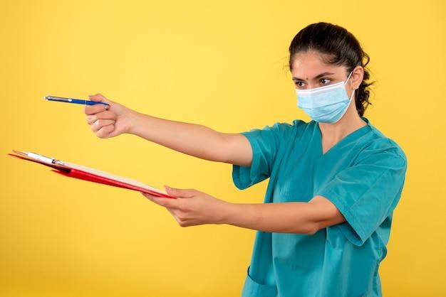 노란색 벽에 서명을위한 클립 보드와 펜을주는 젊은 여성의 전면보기