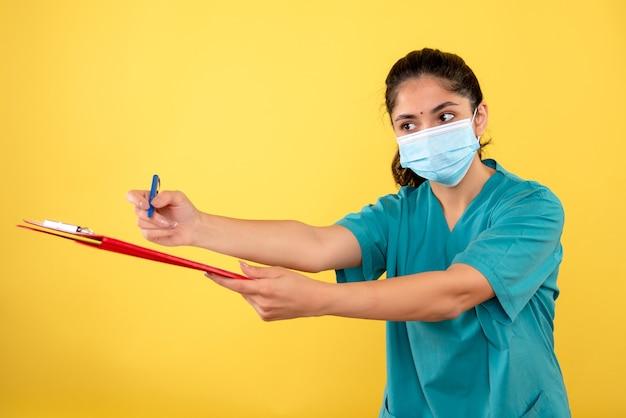 노란색 벽에 서명을위한 클립 보드를주는 젊은 여성의 전면보기