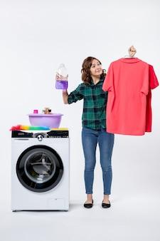 흰 벽에 세탁기에서 깨끗한 옷과 액체 가루를 들고 있는 젊은 여성의 전면