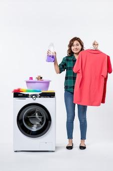 白い壁に洗濯機からきれいな服を保持している若い女性の正面図