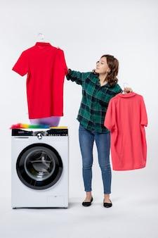 흰 벽에 세탁기에서 바로 깨끗한 옷을 들고 있는 젊은 여성의 전면