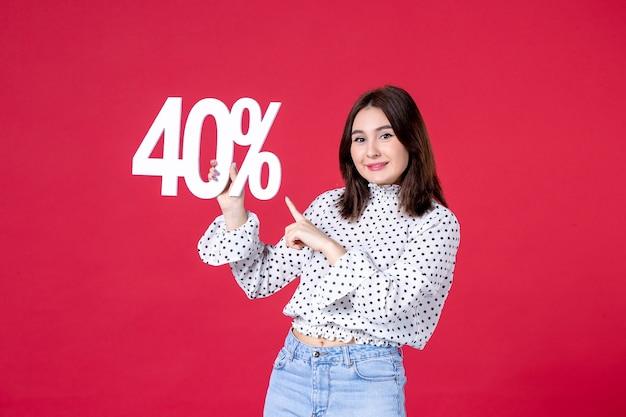붉은 벽에 할인을 들고 있는 젊은 여성의 전면 모습