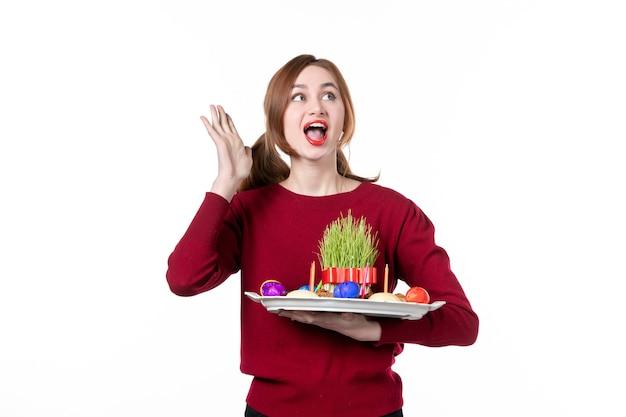 白い背景色のsemeniとnovruzのお菓子とhoncaを保持している若い女性の正面図民族性パフォーマー休日の概念民族の春