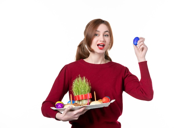 白い背景の概念民族民族休日春色パフォーマーにsemeniとnovruzのお菓子とhoncaを保持している若い女性の正面図