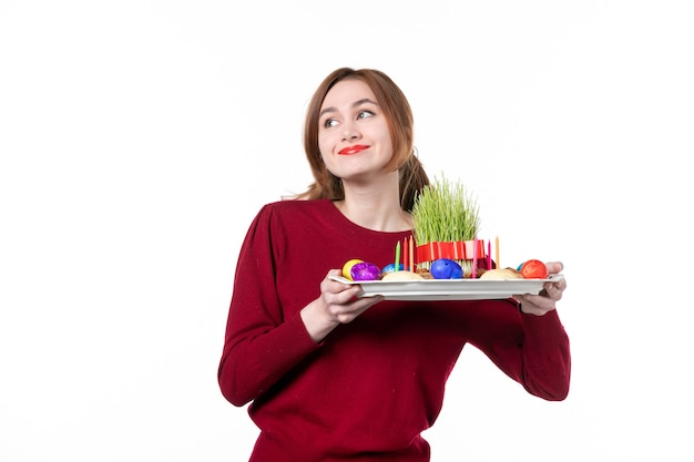 Вид спереди молодой женщины, держащей хонка с семени и новруз сладостями на белом фоне этнический исполнитель этническая принадлежность концепция праздника цвета