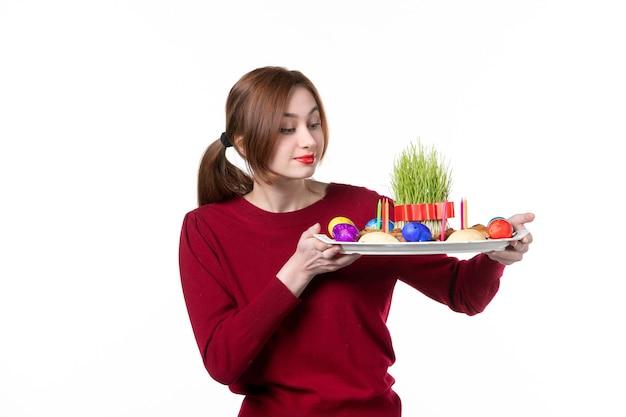 Вид спереди молодой женщины, держащей хонка с семени и новруз конфетами на белом фоне этнический исполнитель этническая принадлежность концепция праздника весенние цвета