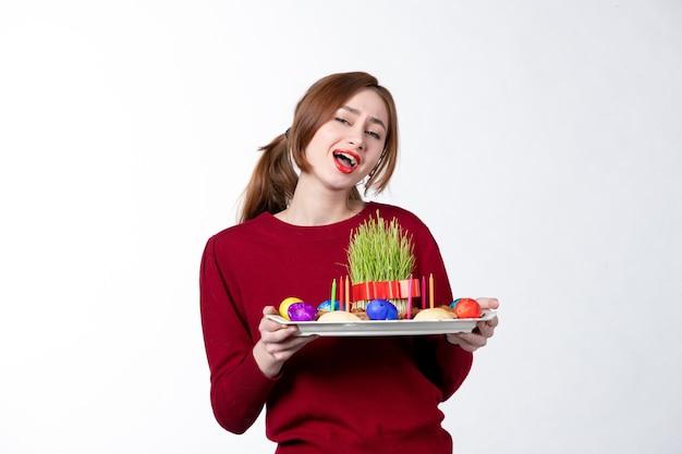 흰색 배경에 semeni 및 novruz 과자를 들고 혼카를 들고 있는 젊은 여성의 전면 보기 민족 공연자 민족성 휴가 개념 봄